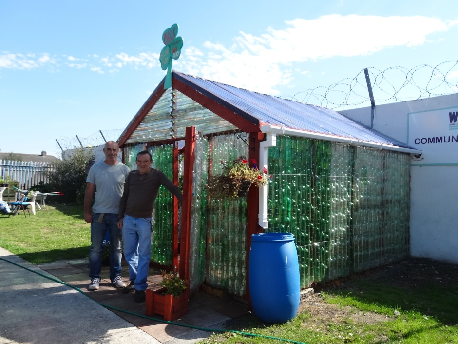 Hubert and assistant Ray outside the plastic bottle greenhouse