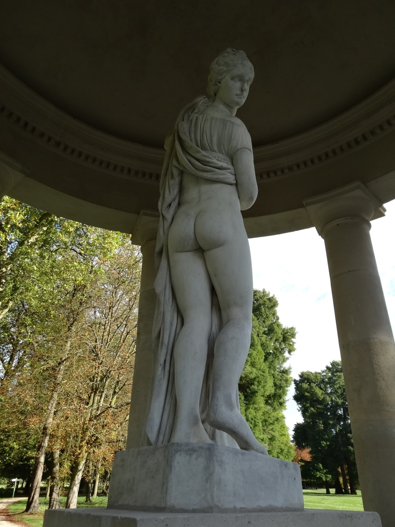 Classic callipygian statue of Venus at Chantilly. Demure on approach but lifts her skirts to reveal her bottom