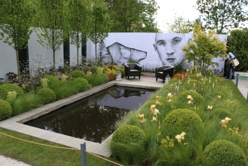 A dominating mural but lovely planting combinations of box globes, grasses and irises.